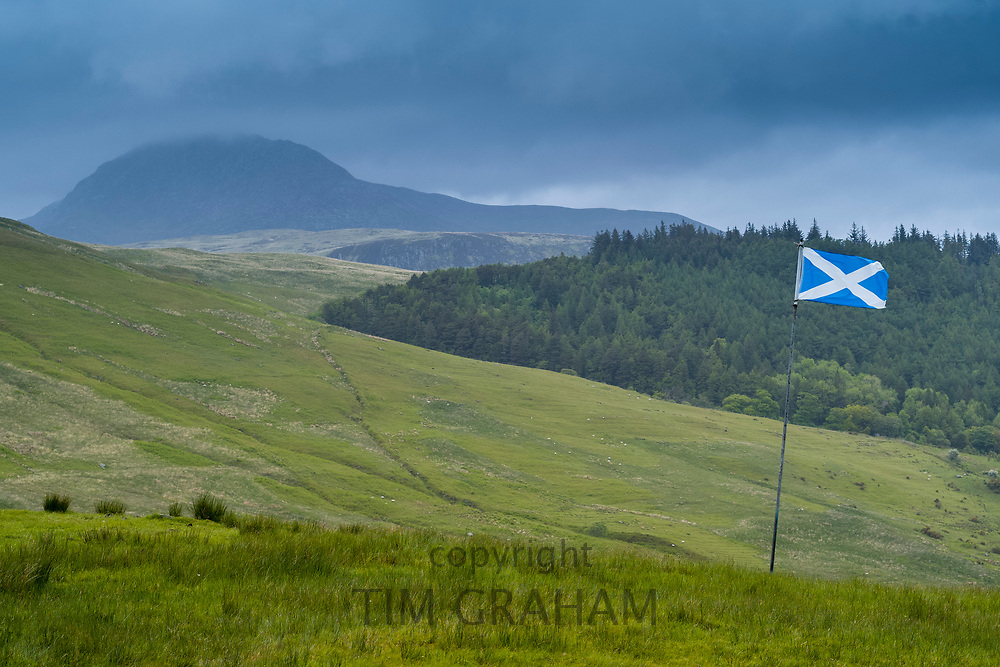 The Flag of Scotland, called The Saltire or Saint Andrew's Cross, flying from a flagpole in typical Scottish landscape, Isle of Arran
