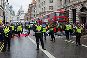 Environmental protesters chain themselves together and glue body parts to the road to block Fleet Street to traffic on the 11th and final day of protests, road-blockages and arrests across London by the climate change campaign Extinction Rebellion, on 25th April 2019, in London, England.