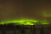 Northern lights over the FInnish forest to the northwest of Inari. forming a shape resembling an eye,