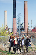 """Boulder, CO (4/27/2010) -- Four climate activists (Kate Clark, Eric Ross, Erik Bonnett and Tom Weis) climbed to the top of the large coal mound in front of the Valmont Power Plant as a rally cheered outside, deploying a banner reading """"RENEWABLES NOW"""" and erecting two mock wind turbines. The activists claimed the coal pile for about 1.5 hours before they were finally taken into custody."""