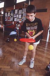 Junior school pupil taking part in sports game during indoor PE lesson,