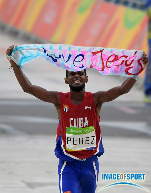 """Aug 21, 2016; Rio de Janeiro, Brazil; Richer Perez (CUB) runs with a """"I love Jesus"""" banner during the marathon during the Rio 2016 Summer Olympic Games at Sambodromo. Perez placed 46th in 2:18:05."""