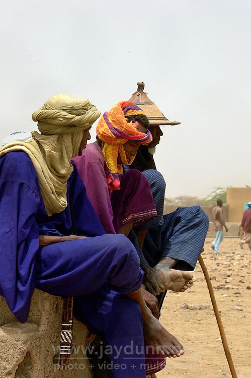 BURKINA FASO, Gorom-Gorom, 2007. A Tuareg, a Bella, and a Fulani nomad share a resting place at Gorom-Gorom's busy Thursday animal market.
