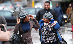 Cape Town - 180629 - Two women crossing Adderly street covers their hair against the rain with plastic bags. While the rain started pouring in Cape Town on Friday, the SA Weather Service has warned that an intense cold front is expected to land on Sunday and continue into Monday. Picture: Henk Kruger/ANA/African News Agency