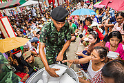 "09 AUGUST 2014 - BANGKOK, THAILAND:  Thai soldiers hand out prepared meals to people at the Ruby Goddess Shrine in the Dusit section of Bangkok. The seventh month of the Chinese Lunar calendar is called ""Ghost Month"" during which ghosts and spirits, including those of the deceased ancestors, come out from the lower realm. It is common for Chinese people to make merit during the month by burning ""hell money"" and presenting food to the ghosts. At Chinese temples in Thailand, it is also customary to give food to the poorer people in the community.        PHOTO BY JACK KURTZ"