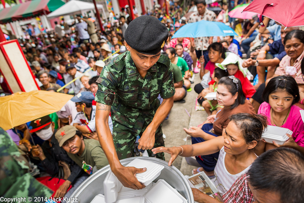 """09 AUGUST 2014 - BANGKOK, THAILAND:  Thai soldiers hand out prepared meals to people at the Ruby Goddess Shrine in the Dusit section of Bangkok. The seventh month of the Chinese Lunar calendar is called """"Ghost Month"""" during which ghosts and spirits, including those of the deceased ancestors, come out from the lower realm. It is common for Chinese people to make merit during the month by burning """"hell money"""" and presenting food to the ghosts. At Chinese temples in Thailand, it is also customary to give food to the poorer people in the community.        PHOTO BY JACK KURTZ"""