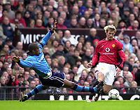 Photo: Greig Cowie<br />Barclaycard Premiership. Manchester United v Manchester City. 09/02/2002<br />Sylvain Distin slides in on David Beckham