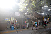 """SHOT 2/2/16 7:57:33 AM - Street scene in Sayulita, Mexico as locals walk past roadside taco stands. Sayulita is a village about 25 miles north of downtown Puerto Vallarta in the state of Nayarit, Mexico. Known for its consistent river mouth surf break, Sayulita was """"discovered"""" by roving surfers in the late 1960s with the construction of Mexican Highway 200. Today, Sayulita is a prosperous growing village of approximately 5,000 residents. Hailed as a popular off-the-beaten-path travel destination, Sayulita offers a variety of activities such as horseback riding, hiking, jungle canopy tours, snorkeling and fishing. Still a mecca for beginner surfers of all ages, the quaint town attracts upscale tourists with its numerous art galleries and restaurants as well. (Photo by Marc Piscotty / © 2016)"""
