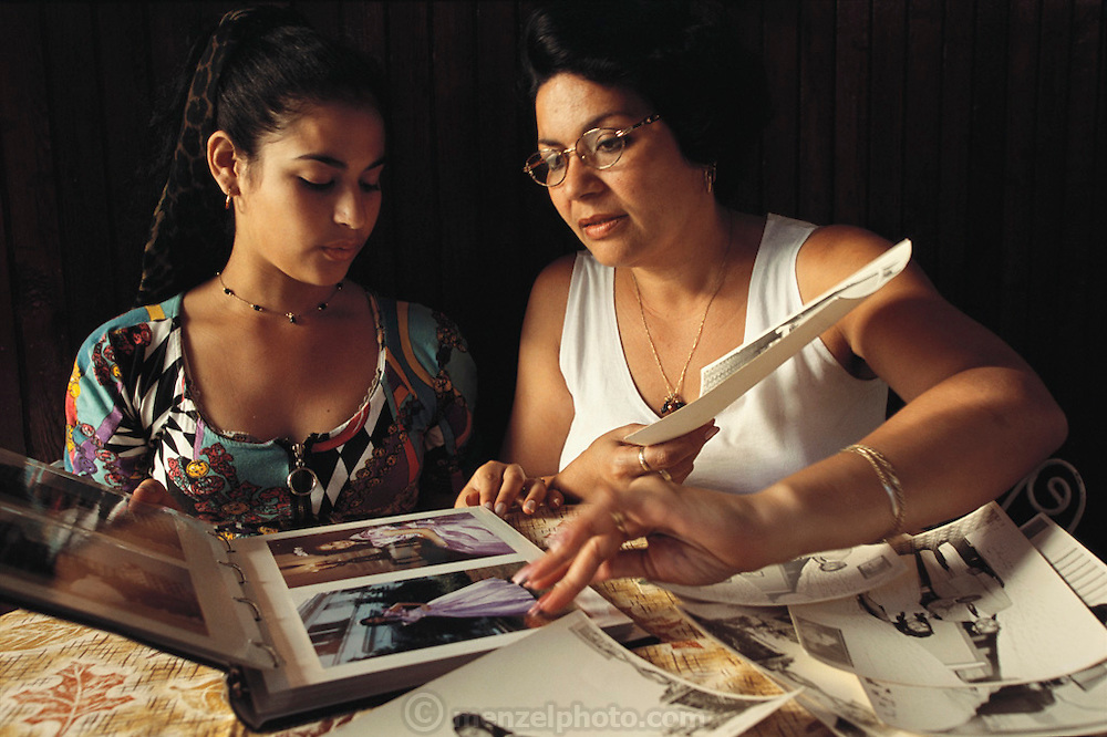 Iris Garcia Costa and her mother Eulina Costa Allouis, compare their respective photos from their traditional 15th birthday parties; a special coming-of-age party for young women called a Quinceañera, or 15th Birthday.