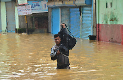 July 19, 2017 - Dimapur, Nagaland, India - An Indian resident wade through flooded area at Dhobinala in Dimapur, India north eastern state of Nagaland on Wednesday, 19 July 2017. Incessant monsoon rain in the region effect normal life causing flood and landslides cutting of the National Highway. (Credit Image: © Caisii Mao/NurPhoto via ZUMA Press)