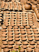 30 OCTOBER 2015 - TWANTE, MYANMAR: Pottery drying in the sun in front of a workshop in the potters' village in Twante, (also spelled Twantay) Myanmar. Twante, about 20 miles from Yangon, is best known for its traditional pottery. The pottery makers are struggling to keep workers in their sheds though. As Myanmar opens up to outside investments and its economy expands, young people are moving to Yangon to take jobs in the better paying tourist industry or in the factories that are springing up around Yangon.     PHOTO BY JACK KURTZ