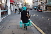 An Asian woman carrying her bags which match her headscarf and sari. London, UK. Colour coordination even while out shopping.