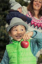 Little boy showing red apple and standing mother with baby in the background, Bavaria, Germany