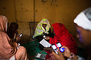 Women teach other how to share music via cell phones days after thier town was liberated from Islamic militants on Jan. 31, 2013.