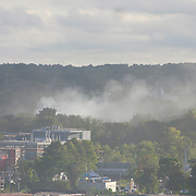 13/09/2018, Lawrence, Massachussets. A gray smoke column rinses from behind the Halloween Palace (Orange building - left.                    Several fires spin out of control after many reported smell gas and gas leaks. People seems shaked. Hundres spend the nights in shelters. Some made frenetical calls to families and friends. The sirens from first responder comes in all direction.                    Some parents we follow rush from work to pick up kids to safer place. Some kids look scare; others cry, a still other play online games.                             | Español                                                    Multiples columnas de humo cubre el cielo de Lawrence. Los fuegos se inicieron en lugares con un fuerte olor a gas liguado, confirmado por el departamento de bomberos. Photo:©George Richardson/ Cinefoto. All right register