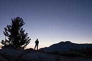 A man awaits sunrise under a crescent moon, Toiyabe National Forest, California