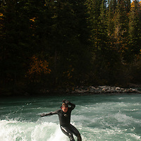 Play boat kayaking and wave surfing on Kananaskis River, Kananskis Provincial Park, near Banff and Calgary, Alberta, Canada
