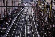 On both sides of the railway track, thousands of commuters desperate to get home after a long day at work in central London, line the platforms to we see from an aerial perspective. But the rail workers' union has called for industrial action and there are no trains yet for these passengers to board for north or southbound services. Sensibly away from the edges, people are standing up to six-deep in anticipation of a ride home as the exodus to the suburbs hits its peak time. 37 per cent of workers in the capital used rail or underground travel as their main form of transport to work, according to regional and local statistics compiled by the Office for National Statistics.