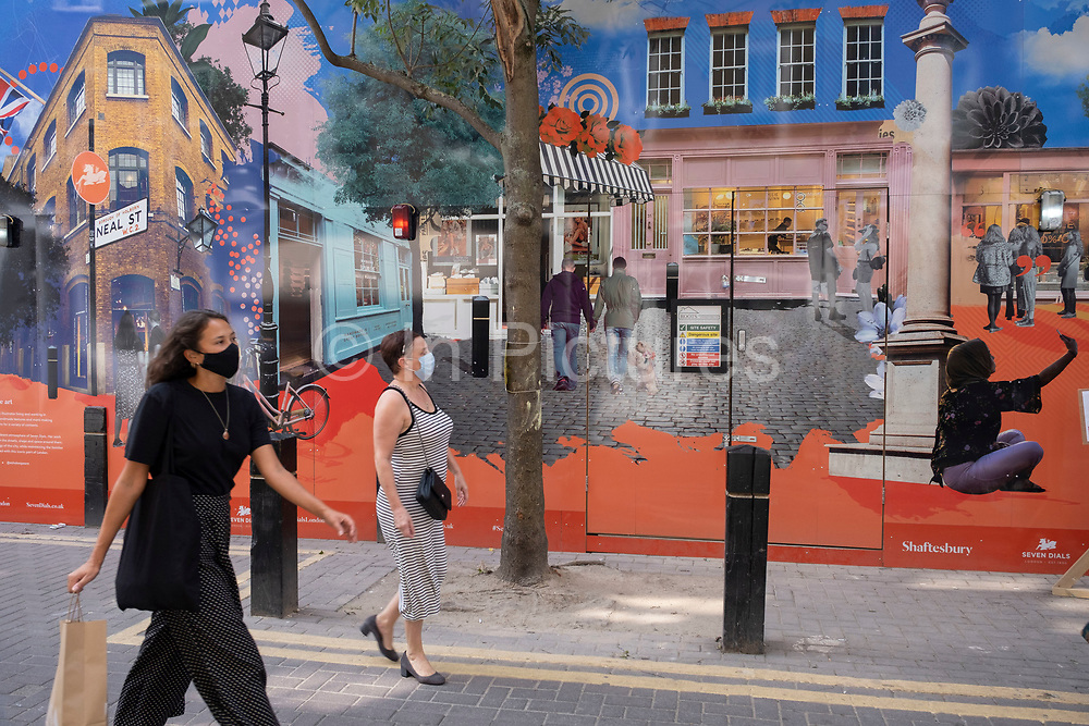 As Britain enters a period of deep recession, with some shops closing either temporarily or permanently as the economic downturn caused by the Covid-19 pandemic cuts hard, people wearing face masks pass a construction site hoarding on Neal Street in Covent Garden on 13th August 2020 in London, United Kingdom. The Office for National Statistics / ONS has announced that gross domestic product / GDP, the widest gauge of economic health, fell by 20.4% in the second quarter of the year, compared with the previous quarter. This is the biggest decline since records began. The result is that Britain has officially entered recession, as the UK economy shrank more than any other major economy during the coronavirus outbreak.