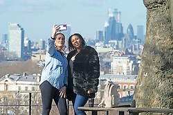 © Licensed to London News Pictures 26/02/2021.        Greenwich, UK. Friends take a selfie together. People get out of their homes from a third national Coronavirus lockdown to enjoy some bright sunny weather in Greenwich Park, London. Photo credit:Grant Falvey/LNP