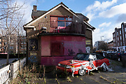 Abandoned car dumped outside a derelict boarded up pub in Whitechapel on 29th January 2021 in London, United Kingdom. The Old Artichoke pub has been closed for twenty years now, since 2001 and was once a popular local Watneys pub in the East End.