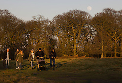 © Licensed to London News Pictures. 26/02/2021. London, UK. People take a walk in Richmond Park as the near full snow moon rises over trees illuminated by the setting sun. Native American tribes in the northeastern United States named February's full moon the 'snow moon' because of the heavy snows that usually fall in that time of year. Photo credit: Peter Macdiarmid/LNP