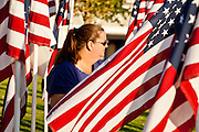 """10 SEPTEMBER 2011 - TEMPE, AZ:     A woman walks through the """"Healing Field"""" in Tempe, AZ, Saturday. The """"Healing Field,"""" a display of 2,996 flags, one for each person killed in the September 11 terrorists attacks on the World Trade Center in New York City and Washington DC, have become an annual tradition in Tempe. The event is sponsored by the National Exchange Club.     PHOTO BY JACK KURTZ"""