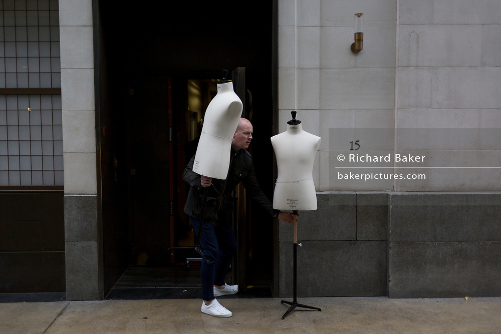 A delivery man carries a delivery of two tailor's dummies to the rear entrance of a West End retailer, on 12th November 2019, in London, England.