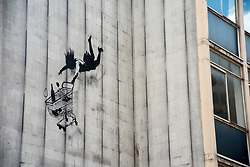 August 4, 2017 - London, England, United Kingdom - Banksy's Falling Shopper is pictured in Central London on August 4, 2017. Falling Shopper is a stencil art piece Banksy painted some meters above street level on the side of a large, disused office building, back in 2011. Showing a well off woman clutching her shopping trolley filled with groceriesm while plummeting from a great height, Falling Shopper was purposely placed in upmarket, high-end shopping district of Mayfair, part of London with a high density of upscale shops. (Credit Image: © Alberto Pezzali/NurPhoto via ZUMA Press)