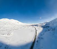 Dronefoto-panorama som viser Sølvfjellet, Spanstinden og E6 vinterstid.