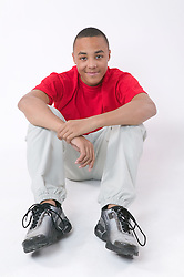 Portrait of a teenaged boy sitting on the floor smiling,