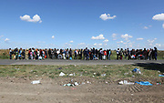 Migrants  queue for a bus close to the Hungarian and Serbian border town of Roszke, Hungary, September 7 2015. The UN's humanitarian agencies are on the verge of bankruptcy and unable to meet the basic needs of millions of people because of the size of the refugee crisis in the Middle East, Africa and Europe, senior figures within the UN have told the media.