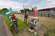 Military aircraft enthusiasts carry step ladders and long lenses past a jizo statue on the way to   Naval Air Facility, Atsugi airbase to watch F18 fighter jets take off. Yamato, Kanagawa, japan. Monday April 29th 2019. The F18 of the Royal Aces squadron is a rare visitor to this US and Japan Self Defence Force base in Kanagawa. Once stationed there the jets, which were the cause of lawsuits related to noise levels by local residents, have been moved to Iwakuni airbase. Many aircraft enthusiasts still turn put to watch and photograph them when they visit however..