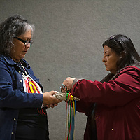 Rowena Becenti, left, and Anna Rondon New Mexico Indigenous Women's Resource Council (NMIWRC) board members participate in a ribbon tying ceremony Saturday in celebration of the launch of the NMIWRC at Rio West Mall in Gallup.