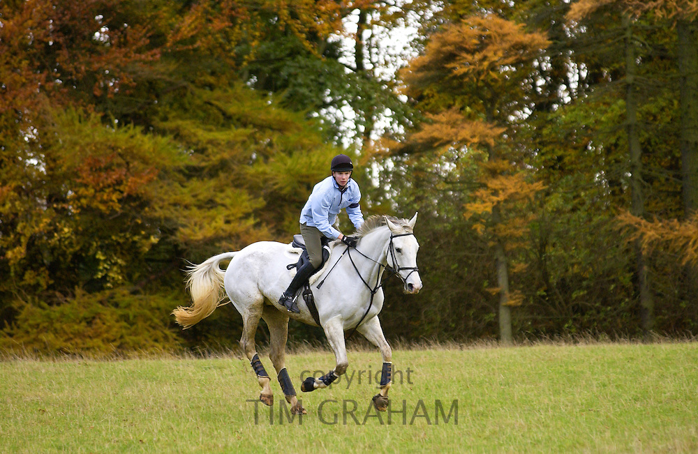 Young man rides Grey mare horse in the Cotswolds, Swinbrook, Oxfordshire, UK