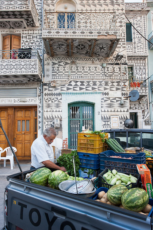 """A wondering greengrocer selling vegetables and fruits from the back of his pick up track parked in a street in Pyrgi, Chios. In the background a typical local house with the decorative motives in the facade- Xysta or sgraffito.<br /> <br /> Pyrgi in Chios is known as the """"painted village"""" on account of the decoration of the houses. The village still keeps its medieval style and together with the other Mastichochoria (Mastic Villages) are in the list of the Intangible Cultural Heritage of Humanity of UNESCO"""