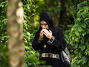 06 JULY 2016 - BANGKOK, THAILAND:  A woman prays in the cemetery at Ton Son Mosque in the Thonburi section of Bangkok before Eid services at the mosque. Eid al-Fitr is also called Feast of Breaking the Fast, the Sugar Feast, Bayram (Bajram), the Sweet Festival or Hari Raya Puasa and the Lesser Eid. It is an important Muslim religious holiday that marks the end of Ramadan, the Islamic holy month of fasting. Muslims are not allowed to fast on Eid. The holiday celebrates the conclusion of the 29 or 30 days of dawn-to-sunset fasting Muslims do during the month of Ramadan. Islam is the second largest religion in Thailand. Government sources say about 5% of Thais are Muslim, many in the Muslim community say the number is closer to 10%.       PHOTO BY JACK KURTZ