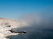 A small wooden hut on the bank of a lake in Jarfjord, near Kirkeness, Finnmark region, northern Norway