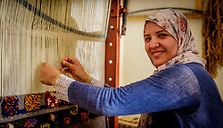 A woman in traditional dress sits weaving carpets in Tazenakht, southern Morocco, Africa<br /> <br /> (c) Andrew Wilson   Edinburgh Elite media