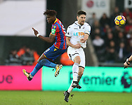Federico Fernandez of Swansea city  is challenged by Wilfried Zaha of Crystal Palace (l). .Premier league match, Swansea city v Crystal Palace at the Liberty Stadium in Swansea, South Wales on Saturday 23rd December 2017.<br /> pic by  Andrew Orchard, Andrew Orchard sports photography.