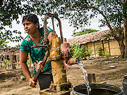 25 MAY 2013 - MAE SOT, TAK, THAILAND:     A Burmese woman, a Roman Catholic of Indian ancestry, pumps water at a well in an unofficial village of Burmese refugees north of Mae Sot, Thailand. They live on a narrow strip of land about 200 meters deep and 400 meters long that juts into Thailand. The land is technically Burma but it is on the Thai side of the Moei River, which marks most of the border in this part of Thailand. The refugees, a mix of Buddhists and Christians, settled on the land years ago to avoid strife in Myanmar (Burma). For all practical purposes they live in Thailand. They shop in Thai markets and see their produce to Thai buyers. About 200 people live in thatched huts spread throughout the community. They're close enough to Mae Sot that some can work in town and Burmese merchants from Mae Sot come out to their village to do business with them.   PHOTO BY JACK KURTZ