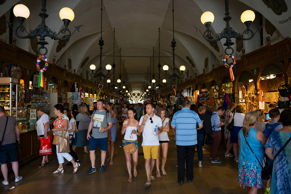 Krakow, Poland - August 26, 2016: Tourists walk through the interior of the Krakow Cloth Hall (Sukiennice), a corridor lined with market stalls selling handicrafts and other products. It is located in Rynek Glowny Square.