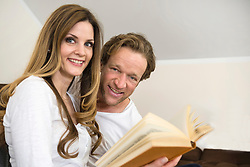 Smiling couple reading book together