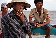 Three fishermen smoke cigarettes and pass the time before they jump off this pier into the South China Sea for some late afternoon fishing. Located in Bac Lieu Province, they will use nets attached to poles to catch fish in the surf. Robert Dodge, a Washington DC photographer and writer, has been working on his Vietnam 40 Years Later project since 2005. The project has taken him throughout Vietnam, including Hanoi, Ho Chi Minh City (Saigon), Nha Trang, Mue Nie, Phan Thiet, the Mekong, Sapa, Ninh Binh and the Perfume Pagoda. His images capture scenes and people from women in conical hats planting rice along the Red River in the north to men and women working in the floating markets on the Mekong River and its tributaries. Robert's project also captures the traditions of ancient Asia in the rural markets, Buddhist Monasteries and the celebrations around Tet, the Lunar New Year. Also to be found are images of the emerging modern Vietnam, such as young people eating and drinking and embracing the fashions and music of the West. His book. Vietnam 40 Years Later, was published March 2014 by Damiani Editore of Italy.
