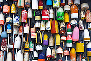Lobster buoys hang in display on a coastal shack. Provincetown, MA