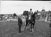 "Guinness Competitions At The RDS Horse Show.(R39)..1986..09.08.1986..08.09.1986..9th August 1986..At the Dublin Horse Show at the RDS, Guinness sponsor several events,The Guinness Match International, The Novice Championship and the Guinness Tankard...Photograph of Stephen Smyth aboard ""Hilton Nelly' winner of the Novice Championship being presented with his trophy by Mr Dick Frost,Guinness Group Sales, included in the picture is Mr Arthur Mallon, Monaghan ,owner of 'Hilton Nelly'."