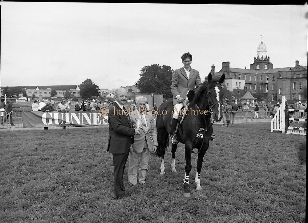 """Guinness Competitions At The RDS Horse Show.(R39)..1986..09.08.1986..08.09.1986..9th August 1986..At the Dublin Horse Show at the RDS, Guinness sponsor several events,The Guinness Match International, The Novice Championship and the Guinness Tankard...Photograph of Stephen Smyth aboard """"Hilton Nelly' winner of the Novice Championship being presented with his trophy by Mr Dick Frost,Guinness Group Sales, included in the picture is Mr Arthur Mallon, Monaghan ,owner of 'Hilton Nelly'."""