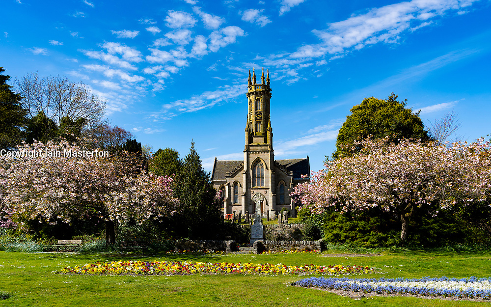 Rhu, Scotland, UK. 24 April 2020. Pink cherry blossom trees frames the Parish of Rhu and Shandon Church in the village of Rhu in Argyll & Bute. Temperatures reached 20C with constant sunshine in the area. Iain Masterton/Alamy Live News