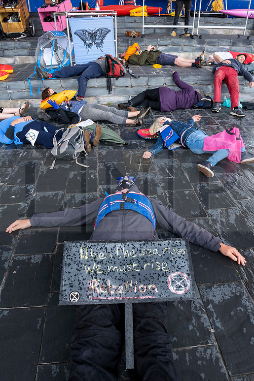 """© Licensed to London News Pictures;02/09/2020; Cardiff, Wales, UK. Extinction Rebellion protest with a symbolic """"drown in"""" in Cardiff Bay in front of the Senedd, the Welsh Government building, in support of the upcoming Climate and Ecological Emergency Bill. Today the protest is """"Rising Tide Action!!"""" focusing on the impact that the climate crisis is having locally and across Wales because it is impacting weather cycles, flooding, air pollution and our food security. The protest involved arts, theatre, speakers, music, banners and a drown in. The protest is part of a national protest over the next two weeks including London and other cities in the UK against climate change. XR say that despite clear scientific evidence of the deadly climate and ecological emergency, the UK government are refusing to take the urgent action needed to avoid mass extinction, and that politicians need to support the Climate and Ecological Emergency Bill. During the coronavirus covid-19 pandemic, climate change is being forgotten but it is still an emergency that is happening. The protest was socially distanced and participants wore masks. Photo credit: Simon Chapman/LNP."""