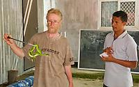 British herpetologist Mark O'Shea holds a Sunda Island pitviper, Cryptelytrops insularis. Watching is Timorese student Benny Carvalho. Bakhita Mission, near Eraulo, Ermera District, Timor-Leste (East Timor)